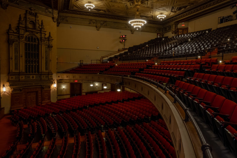 Side view of the red upholstered chairs of the orchestra, loge and balcony at the Sydney Goldstein Theater