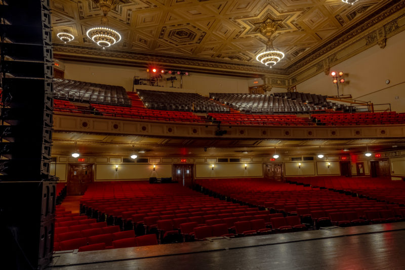 View of the theater seating from stage left, with a stack of Meyer Sound speakers on the side